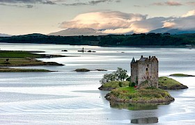 Castle Stalker with lismore in the background on Loch Linnhe with Hebrides Cruises