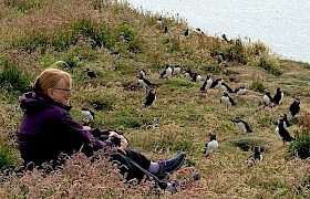 Guest surrounded by puffins Treshnish Isles Cruise Chris Gomersall
